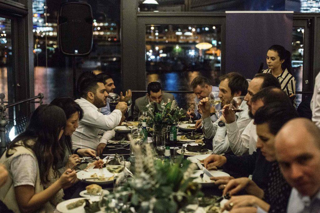 People sitting around long table eating Barramundi