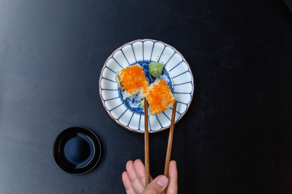 Person picking up sushi with Chopsticks on dark blue matte background
