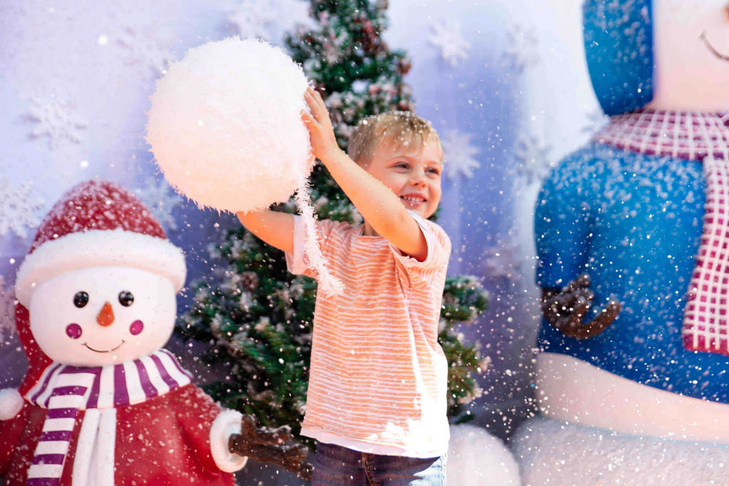 Event PR photography for Christmas wonderland child holds up fake snowball
