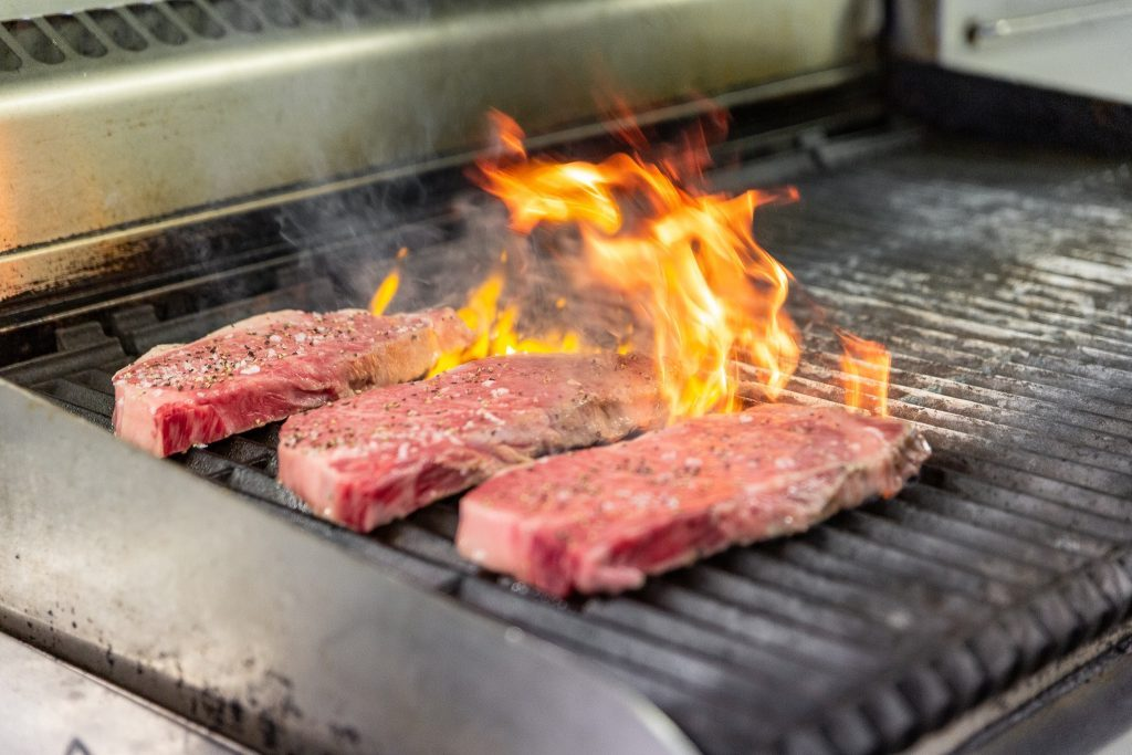 Wagyu Beef steaks cooking on a grill with flames