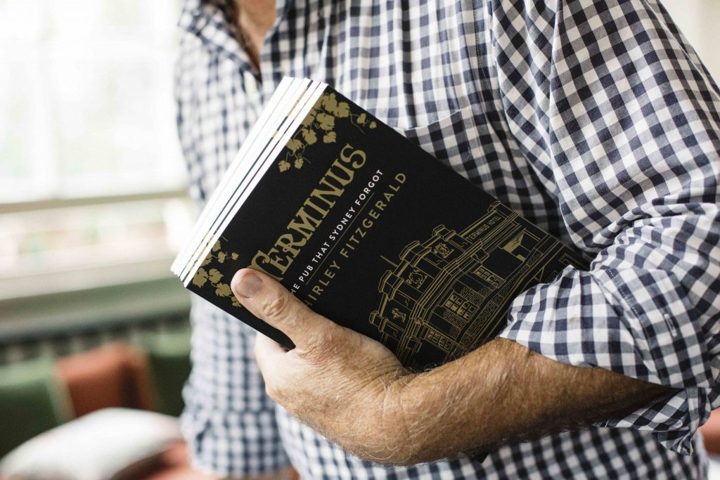 man clutch a copy of the novel about the pub of the same name 'the pub that sydney forgot'