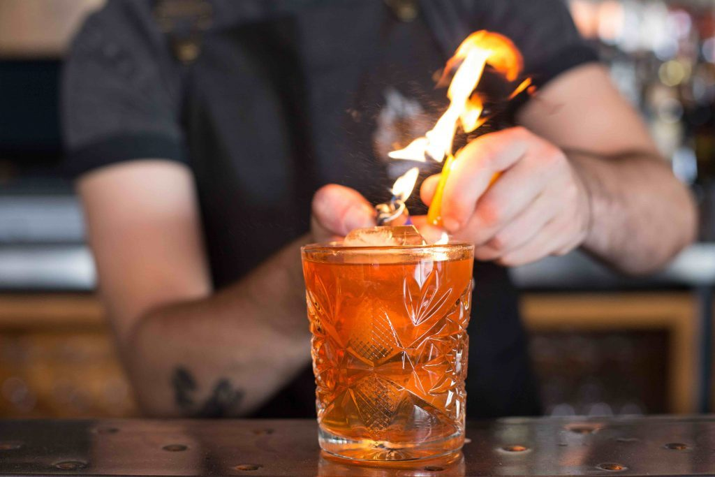 Social Media Marketing Photography Old fashioned cocktail sitting on bar as bartender garnishes drink with flaming orange peel
