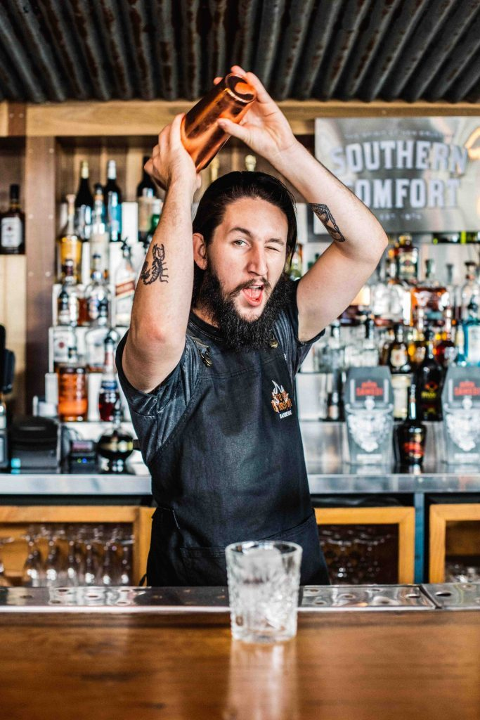 Photography Bartender shaking a cocktail above his head while winking at the camera