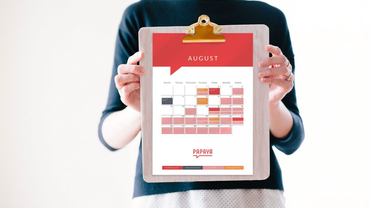 Woman holding calendar with 'fun' holidays tracked across it