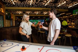 Functions Marketing example from The Oaks Neutral Bay, two people cheers next to air hockey table at Taffys sports bar