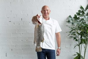 Celebrity Chef Matt Moran holds fish in front of white wall for national barramundi day Media Campaign