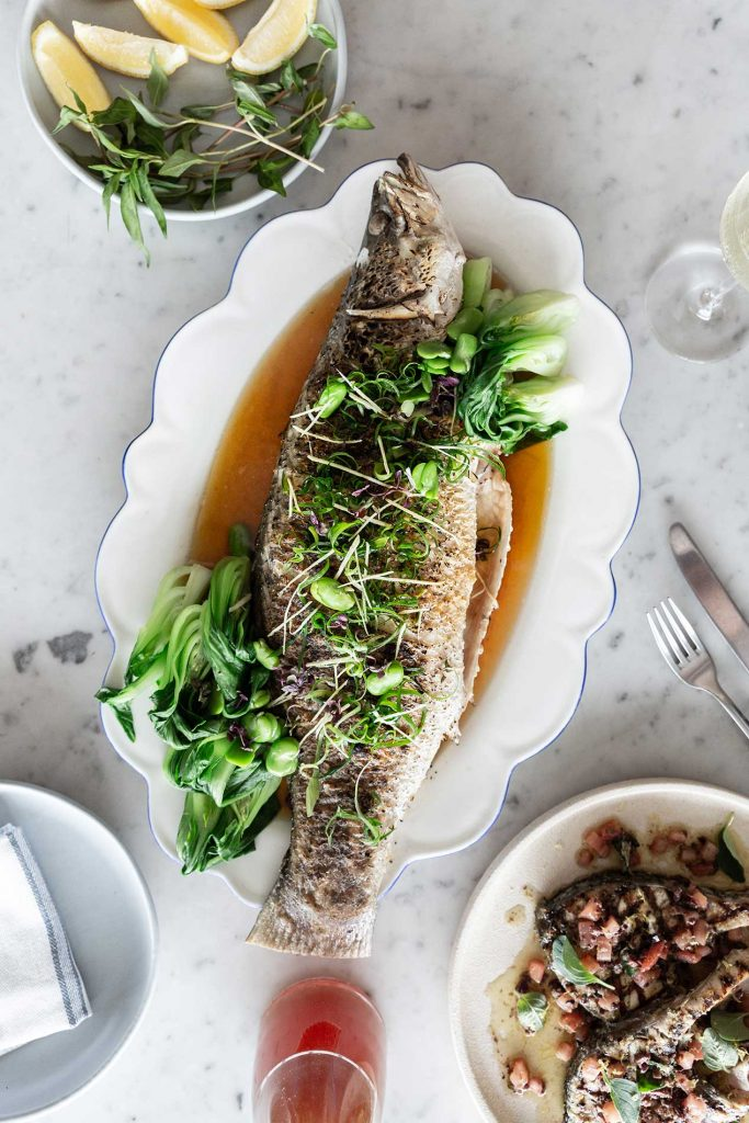 Flatlay of Barramundi dish on marble table top in preparation for media in national barramundi day campaign