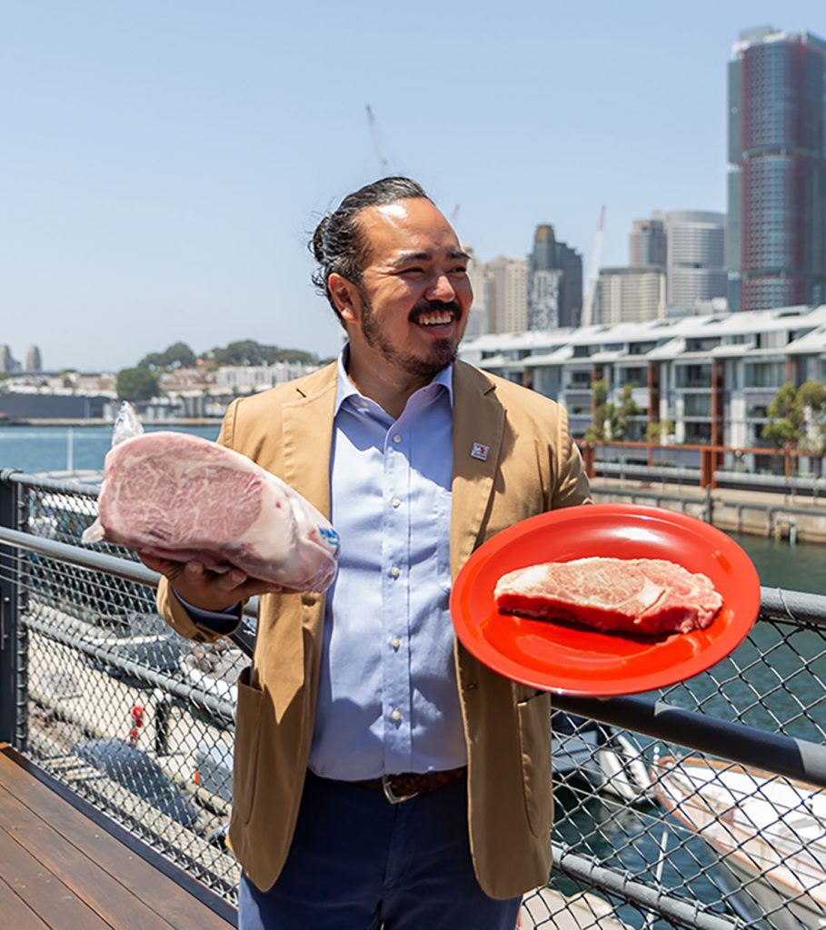 Adam Liaw Food marketing event for japenese Wagyu as he holds two cuts of meat in front of harbour