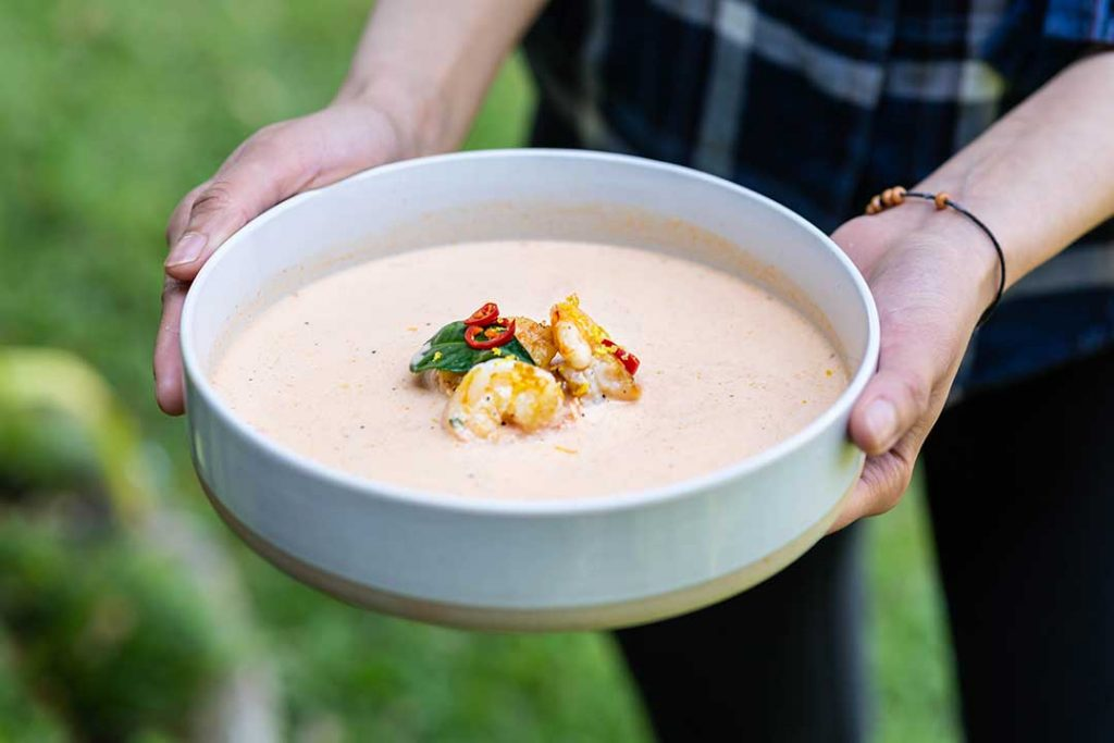Recipe photoshoot of a prawn bisque held in bowl