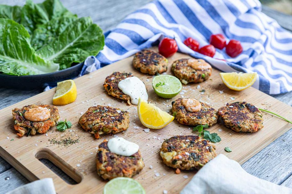 Recipe Photoshoot of fish cakes with sauce and lemon on wood board
