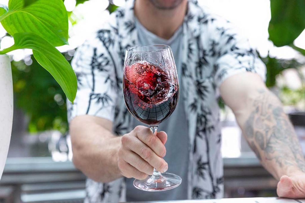 Photo of man swirling red wine in glass for pr campaign