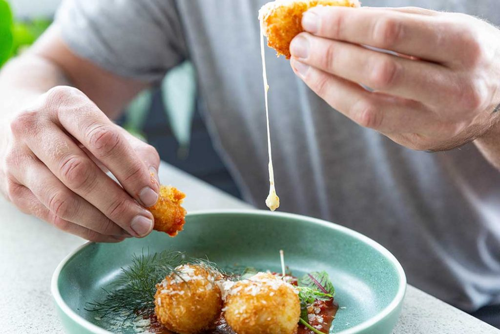 man pulling apart arancini balls with melting cheese dripping