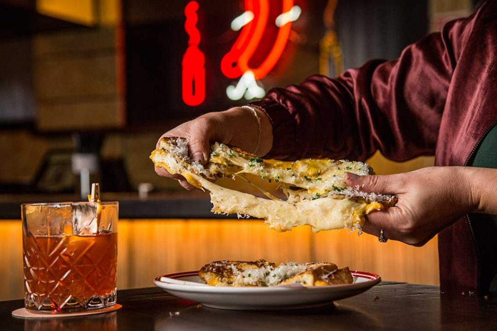 Man pulls apart very cheesy toastie with old fashioned cocktail in bar