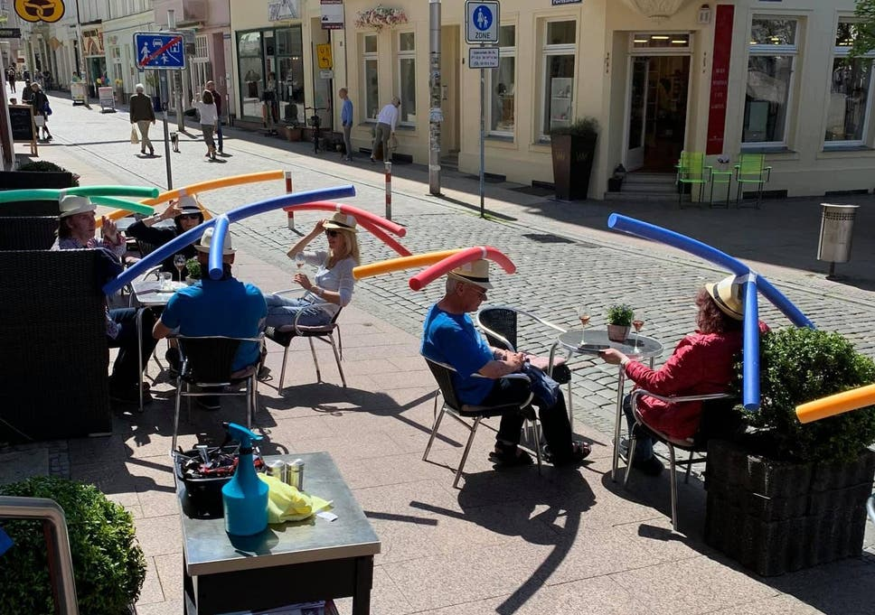People sitting at sunny cafe with noodles on heads to social distance