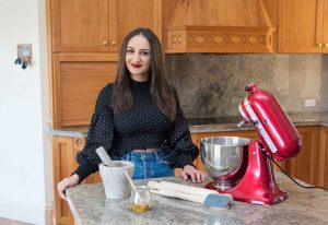 Celebrity chef influencer stands at counter in kitchen with appliances