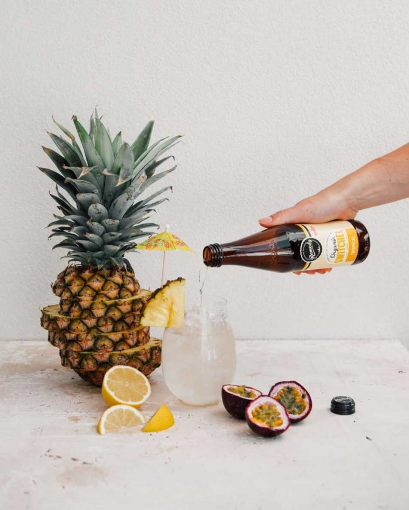 Remedy beverage image- pouring a drink into a glass with tropical fruit around